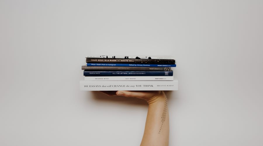 hand presenting pile of books