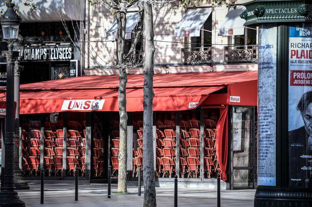 这张摄于2020年11月12日的照片显示了在巴黎香榭丽舍大道上一家封闭餐馆内的椅子上存放的椅子,这是在法国第二次全国禁闭期间,目的在于遏制由新型冠状病毒引起的Covid-19大流行的蔓延。.png